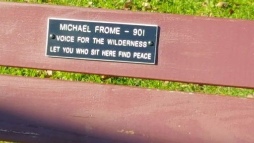 Red-colored park bench with plaque celebrating Michael Frome's 90th birthday. A gift from his wife, June.