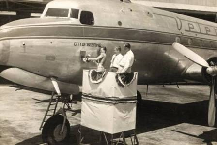 Opal Harris christens Veterans Air Express DC-4 with bottle of orange juice in Sebring FL in July 1946