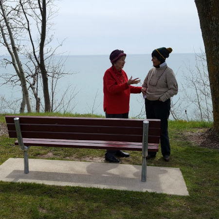 Crisp May morning bundled in wool caps with placid Lake Michigan behind them, June shares her Michael memories with Gaye Lyn.