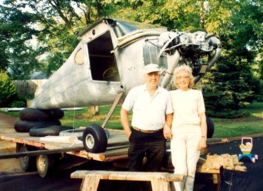 John and Marge Noll stand in front of the Cessna 120 perched on a travel trailer. No wings, no doors.