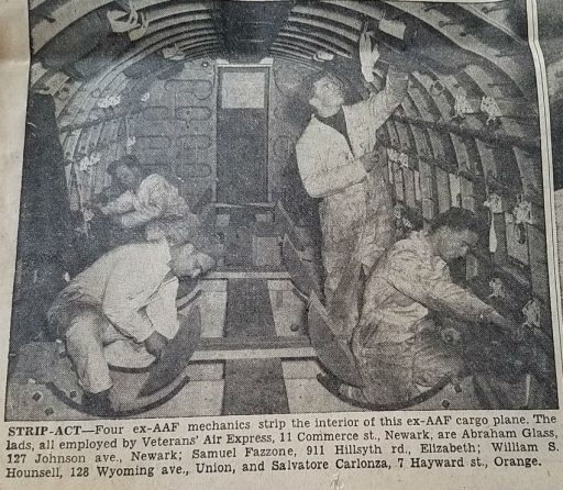 Interior of Veterans Air Express (DC-3) aircraft devoid of seats and all appointmenets. Just four young mechanics hard at work refittig it.