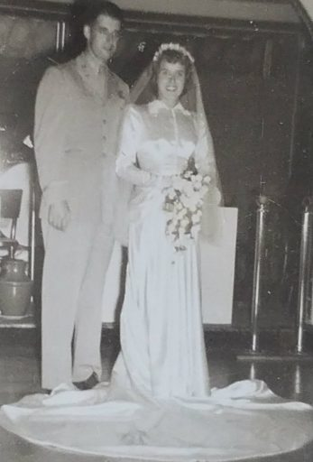 Newlyweds, Mr. and Mrs. Richard Broughton. He in uniform and bride in exquiste floor-length wedding dress and drapped train.