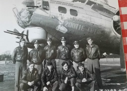 A 10-man crew stand and hunker in front of a B-17 bedecked with hand-painted insignia of Zootie Cutie. Command Pilot Richard Broughton stands 3rd from our left.