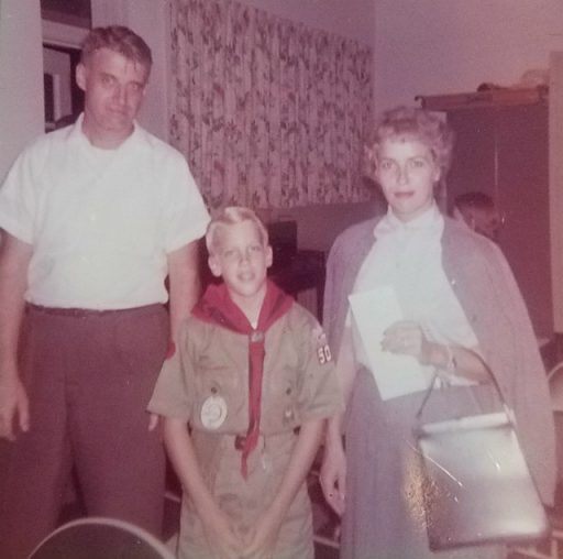 Handsome young Bob Broughton dressed in a Boy Scout uniform stands proudly between his mom, Anna, and dad, Dick Broughton.