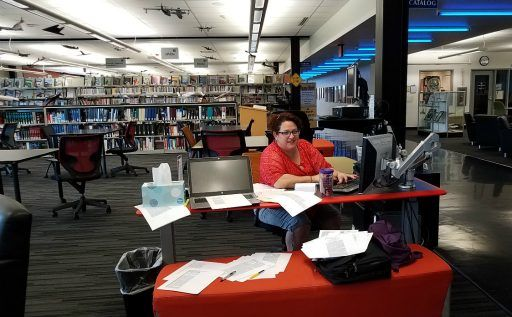 Research Librarian Suzie Roth smiles from behind a stash of clippings she unearthed in search of Veterans Air elusive records. Overhead aircraft models strafe the Hazy Library ceiling.