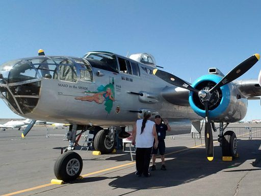 "Shiny metal air frame and glass gunnery perch and cockpit of the fully restored 1944 B-25 named ""Maid In the Shade"" on the ramp at Santa Fe airport."