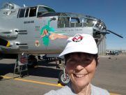 "Behind Gaye Lyn (wearing a big grin) is the nose of restored B-25 named ""Maid in The Shade"" wearing her brightly-colored hand-painted design typical of airplane art of WWII."
