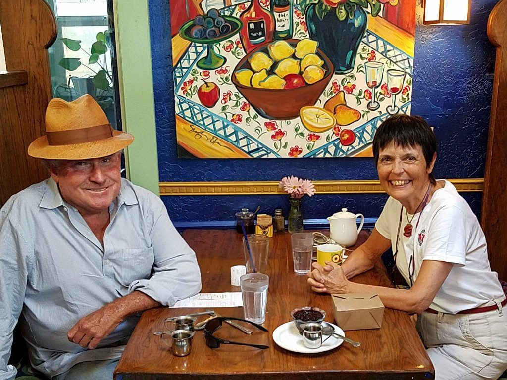 Professor Alan Bender sporting a Panama-style hat sits across the table from Gaye Lyn. A painting of bright yellow lemons and fruit hangs over the table in their booth.