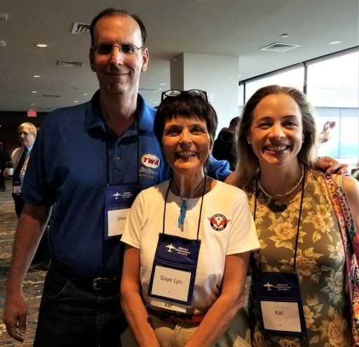 Shea & Kat Oakley stand behind Gaye Lyn, wearing A.I. Convention badges and smiling for the camera.
