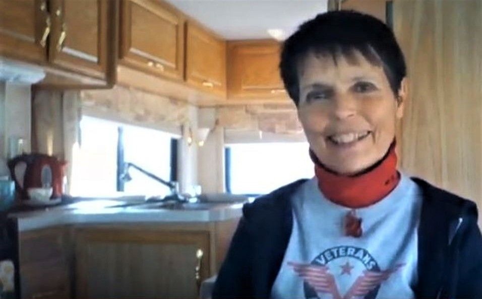 Wearing a Veterans Air T-shirt and big smile, Gaye Lyn sits inside Gracie, her RV, with kitchen and sunlight in background.