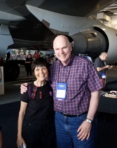 Happy to know each other, David Stringer and Gaye Lyn smile big standing together in the Delta Flight Museum exhibit hall.