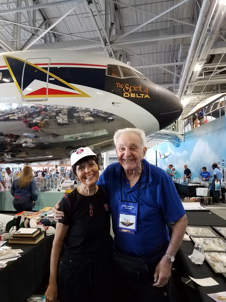 Stanley Baumwald and Gaye Lyn with delighted smiles stand with a 767 towering behind them in the Delta Flight Museum.