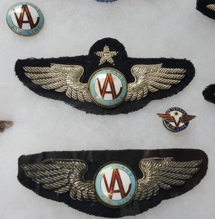 Four Veterans Air Line insignia, each a different design, three carrying stylized initials VAL in the center. PHOTO CREDIT: Website of Charles Quarles.
