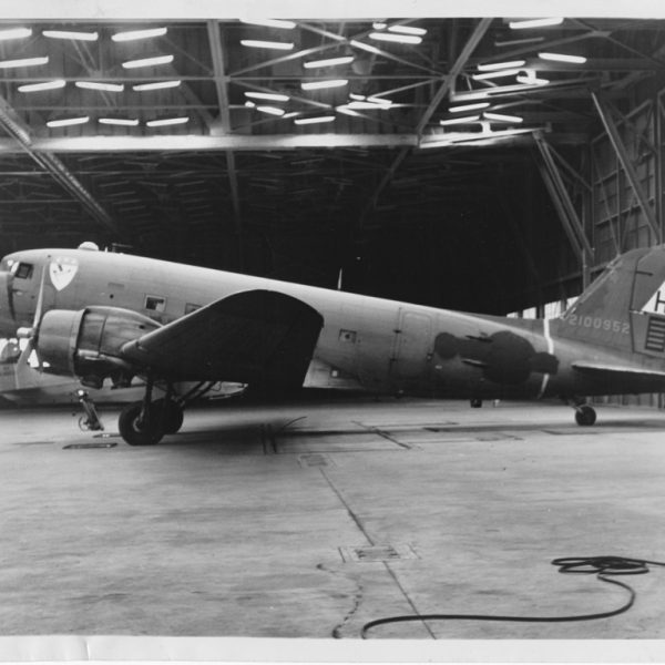A very drab looking hulk of an aircraft stands at the ready for its new civilian life in a military hangar.